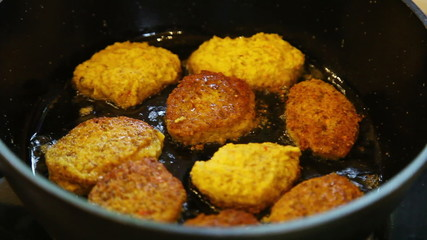 Closeup of turning frying vegetarian cutlets from lentil