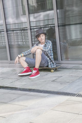 Young boy sitting on skateboard
