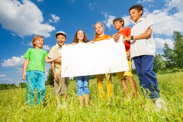 Children holding rectangular shape paper together