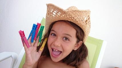 Niña con pinzas de colores en la mano