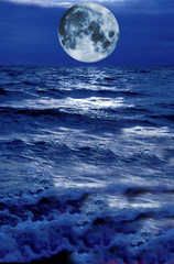 moon rising over stormy blue waters