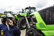 modern farmer and latest tractor models in a line-up