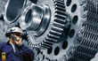 engineer, worker with a giant gears and cogwheel machinery