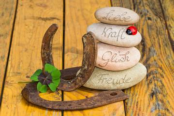Steinturm, Hufeisen, Klee und Marienkäfer auf Holz, Liebe, Glück