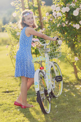 Summer joy -  girl with bicycle in summer garden