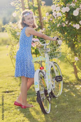 Summer joy -  girl with bicycle in summer garden
