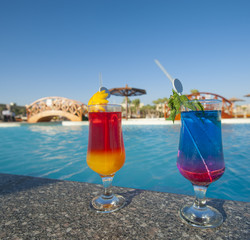 Two cocktail drinks by a tropical pool