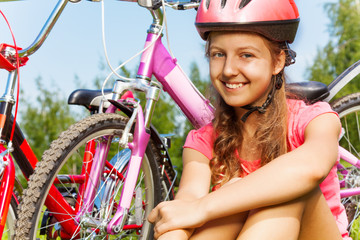Young girl in red helmet with bike on meadow