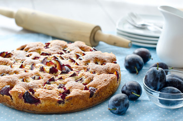 Homemade baked cake with plums on the table