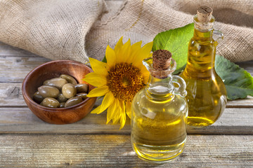 Sunflower and olive oil on rustic wooden background