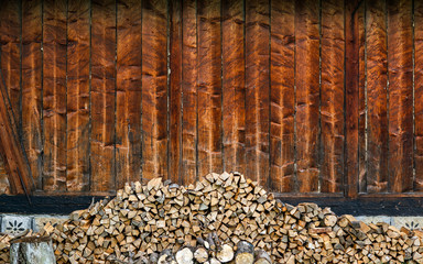 Choped firewoods near wooden wall.