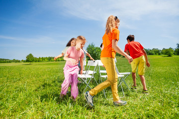 Children run around chairs playing a game outside