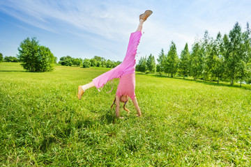 Active girl making flip on grass outside