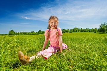 Girl stretching legs apart on grass