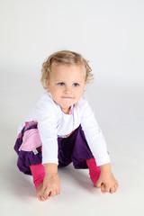 lachendes kleines Mädchen mit lila Hose