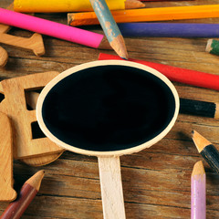 blank chalkboard label and colored pencils on a rustic wooden ba