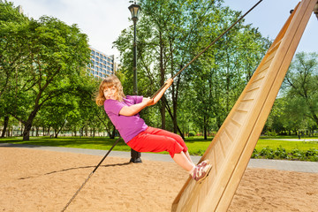 Girl climbing on wooden construction in the park