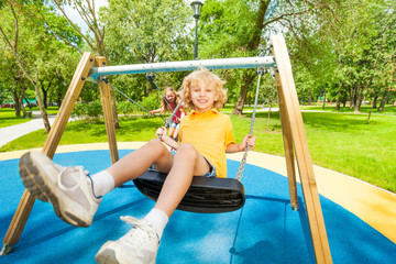 Boy and girl swing in opposite directions