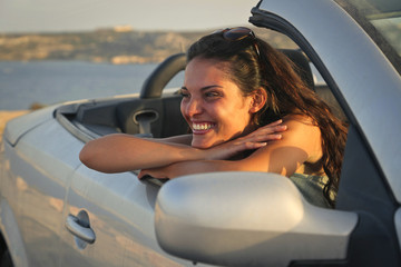 happy woman who is driving an elegant car