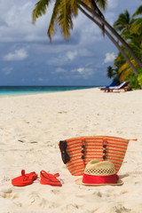 hat, sun glasses and flip flops on a tropical beach