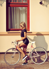 Attractive young woman with vintage bycycle on the street