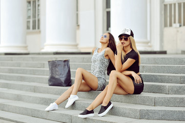 Two young girl friends sitting together. Outdoor fashion portrai