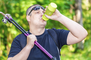 Man with water bottle and walking sticks