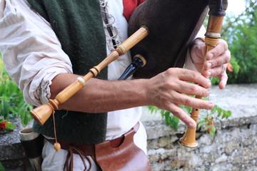 musicista impegnato con strumento musicale cornamusa