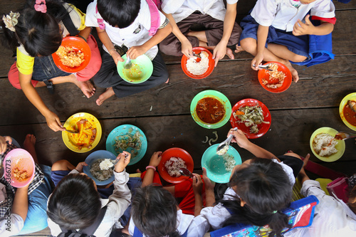 Leinwanddruck Bild Children having lunch in asian school