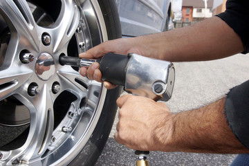 Auto mechanic changing car wheel