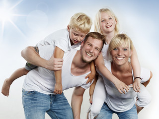Parents giving piggyback ride to children outside