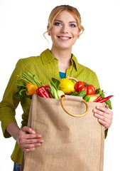 Portrait of happy young woman holding a shopping bag full of gro
