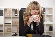 Cold businesswoman warming up with coffee