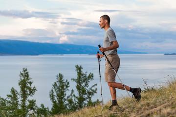 Hiker go down with trekking sticks