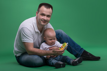 Father and toddler son playing with toy cell phone