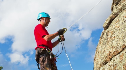 Man Climbs Up on top of the Rock