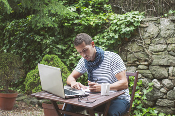 Young man working with laptop in outdoors.
