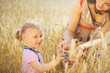 Little girl with young mother at grain wheat field