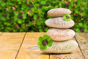Steinturm und Kleeblätter auf Holz, Liebe, Kraft, Glück, Freude