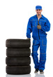young car mechanic with pile car tires
