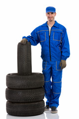young car mechanic with tires for the car