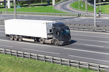Container driving on highway with white refrigerator semitrailer