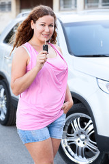 Curly hair woman in pink clothes showing car key in hand