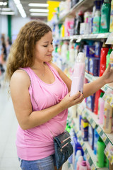 Woman customer looking at the conditioner for linen in shop
