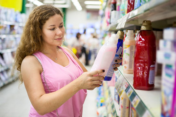 Attractive woman choosing conditioner for washing in shop