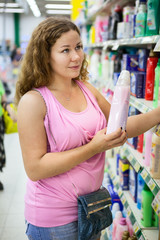 Young attractive woman choosing conditioner for washing in shop