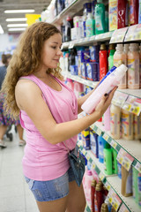 Young Caucasian woman choosing cleaning detergent in shop