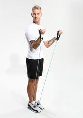 Ćwiczenia z gumami. Mężczyzna rozciąga mięśnie