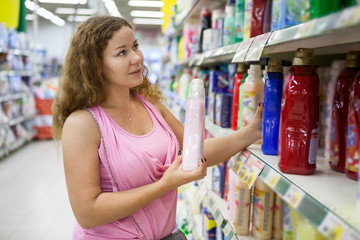 Woman purchaser looking at the conditioner for linen in shop