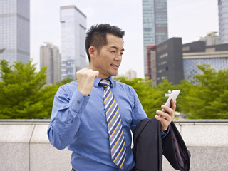 asian business executive reading text message